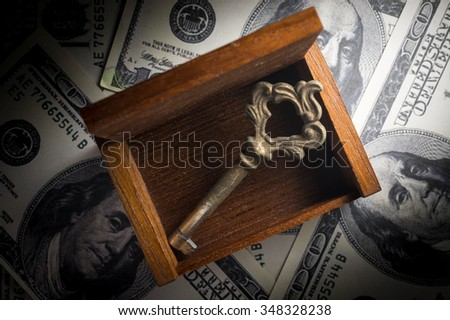 Old key and wooden chest on money. - stock photo