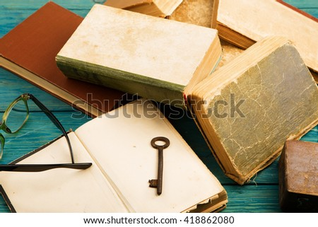 Old key, glasses and stack of antique books on blue wooden background - stock photo