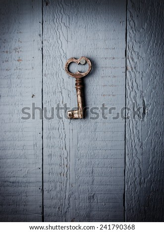 Old key hanging on wooden wall - stock photo