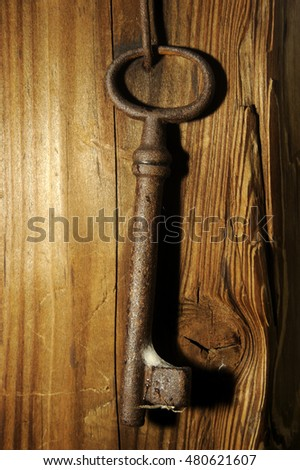 old key hanging on wooden wall.