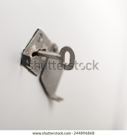 Old key in keyhole - stock photo