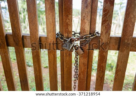 old key lock locked with a chain on wooden door - stock photo