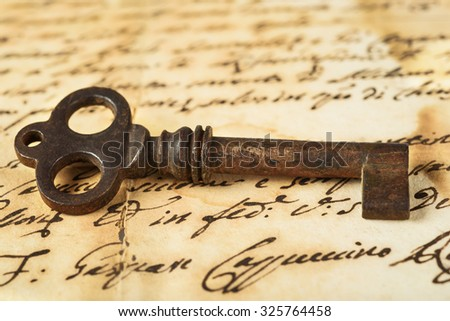 Old key on letter background - stock photo