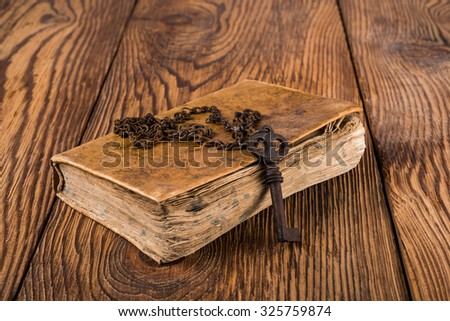 Old key with chain on an book - stock photo