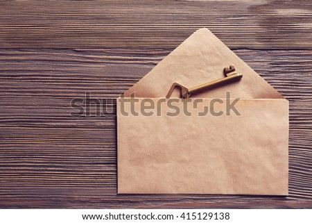 Old key with envelope on wooden background - stock photo