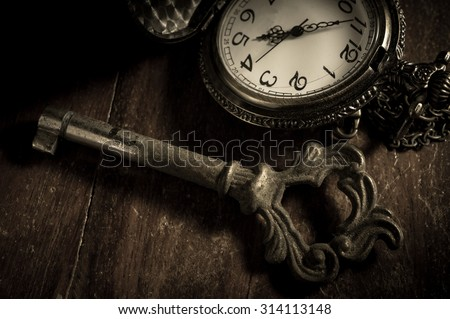 Old key with pocket watch,vintage filtered.