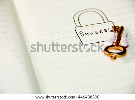 old key with success word on notebook.