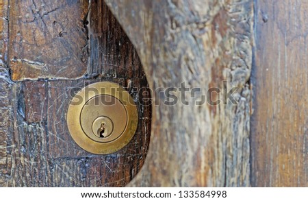 old keyhole on an old wooden door - stock photo