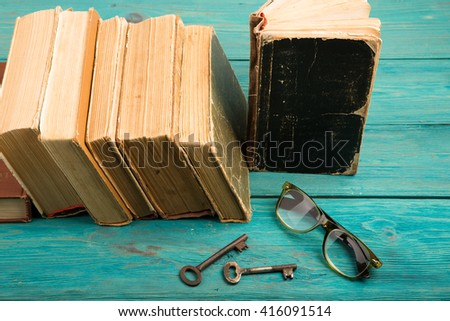 Old keys, glasses and stack of antique books on blue wooden background - stock photo