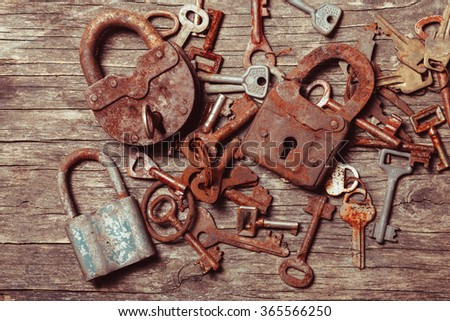 old keys locks over vintage wooden table - stock photo