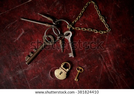 Old keys on the dark red background with small lock - stock photo