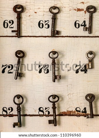 Old keys with numbers hanging on a weathered wall of an old hotel - stock photo