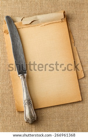 Old knife on yellowed paper - stock photo