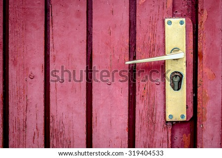 Old knob on a red wooden door
