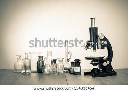 Old laboratory glass and retro microscope vintage sepia photo - stock photo