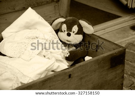 Old lace in wooden chest and vintage plush mouse toy at the entry to antiquities shop in France. Aged photo. Sepia. - stock photo