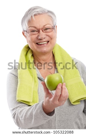 Old lady after workout holding green apple, smiling. - stock photo
