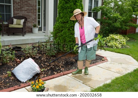 Old lady at work in the garden cleaning flowerbeds ready for transplanting her new flowering plants purchased at the nursery - stock photo