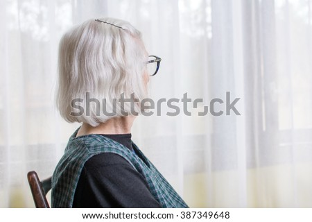 Old lady looking at her window to outdoors - stock photo