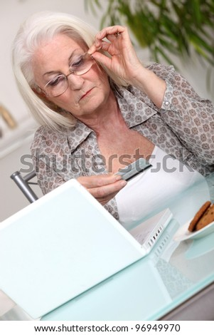Old lady shopping on line - stock photo
