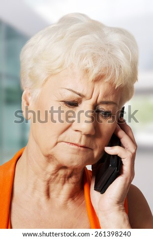 Old lady talking through phone, receiving bad news. - stock photo