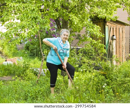 Old lady working in garden in summer, digging with spade. - stock photo