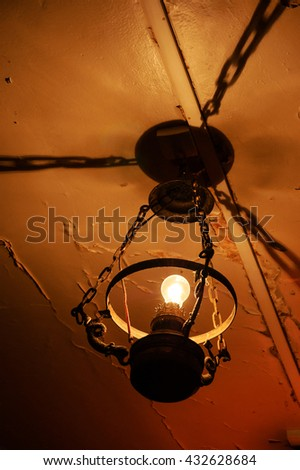 Old lamp hanging from damaged ceiling. Destruction concept. - stock photo