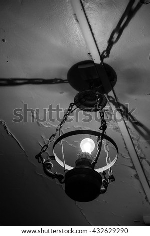 Old lamp hanging from damaged ceiling. Destruction concept. Black and white photo. - stock photo