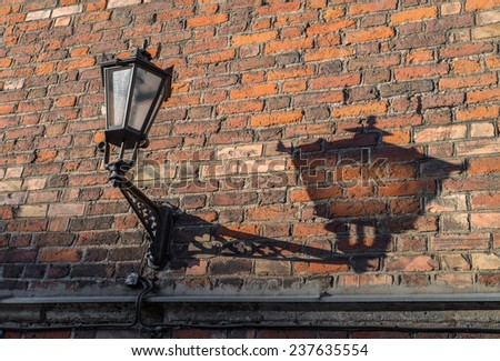 Old lamp lantern on the stone wall, with shadow, process in vintage style picture - stock photo