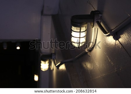 Old lantern lights on a wall at night - stock photo