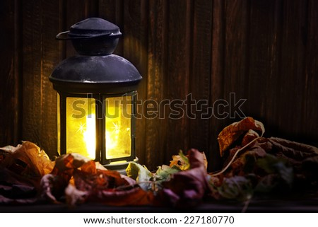old lantern on wooden boards buried autumn leaves