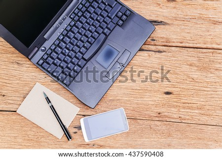 Old laptop with paper note and pen on wood background. - stock photo