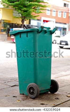 Old large wheel bin on sidewalk - closeup - stock photo