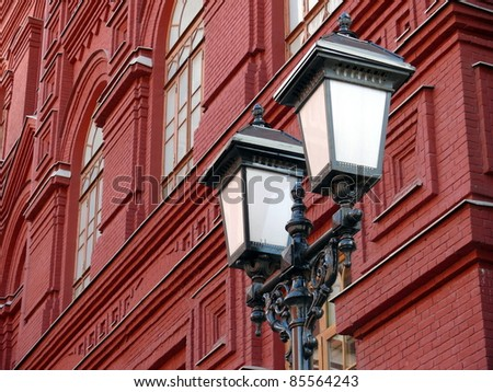 Old latern in red brick wall background - stock photo