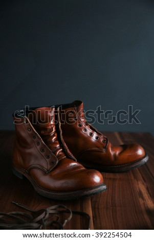 Old leather ankle boots being greased and oiled, laces off