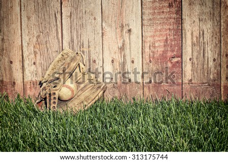 Old leather baseball mitt and ball on grass field against a rough wooden fence - stock photo