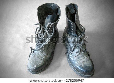 old leather military boots with dust on gray background.
