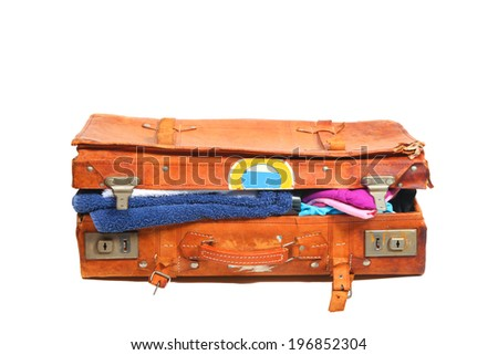 Old leather suitcase overstuffed with clothes  - stock photo