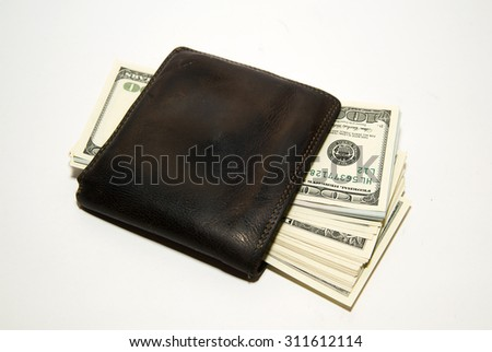 Old leather wallet with banknotes of US dollars inside