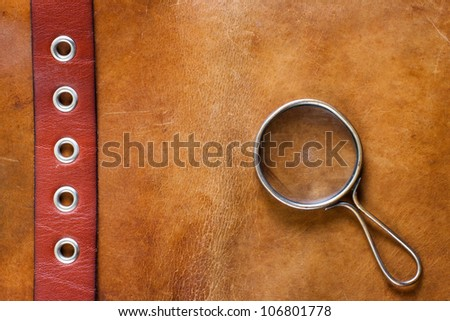 Old leather with magnifying glass - stock photo