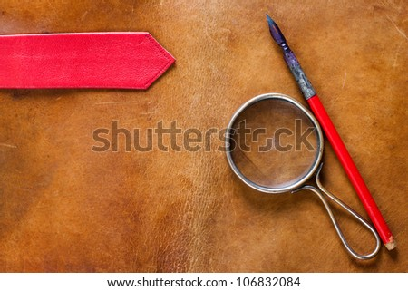 Old leather with magnifying glass and ink pen - stock photo