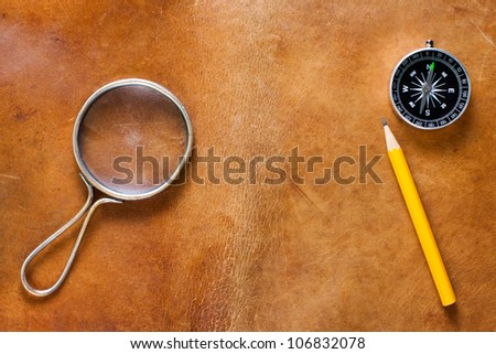 Old leather with magnifying glass, compass and pencil - stock photo