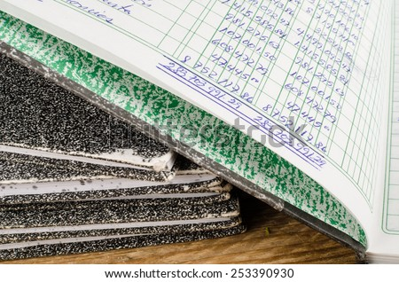 Old  ledger books,  the top one open and displaying handwriting - stock photo