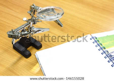 old Lens scope on wood table background - stock photo