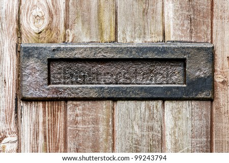 Old letter box in a wooden paneled door - stock photo