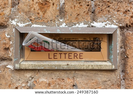 Old letter slot with newspaper closeup. - stock photo