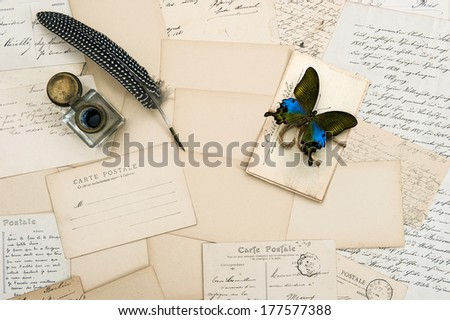 old letters, handwritings, vintage postcards and antique feather pen. nostalgic sentimental background with butterfly - stock photo