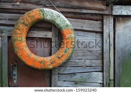 Old lifebuoy hanging against a wooden plank wall of an abandoned boathouse - stock photo
