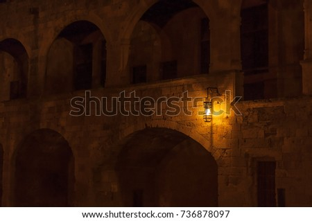 Old light at night hanging on a medieval street fortress wall