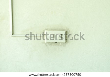 Old light switch on the green wall - stock photo